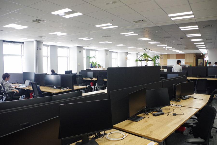 PCや手回り品を持ってどこにでも座れるフリーアドレスのオフィス。デスクは高さも自由に変更できる