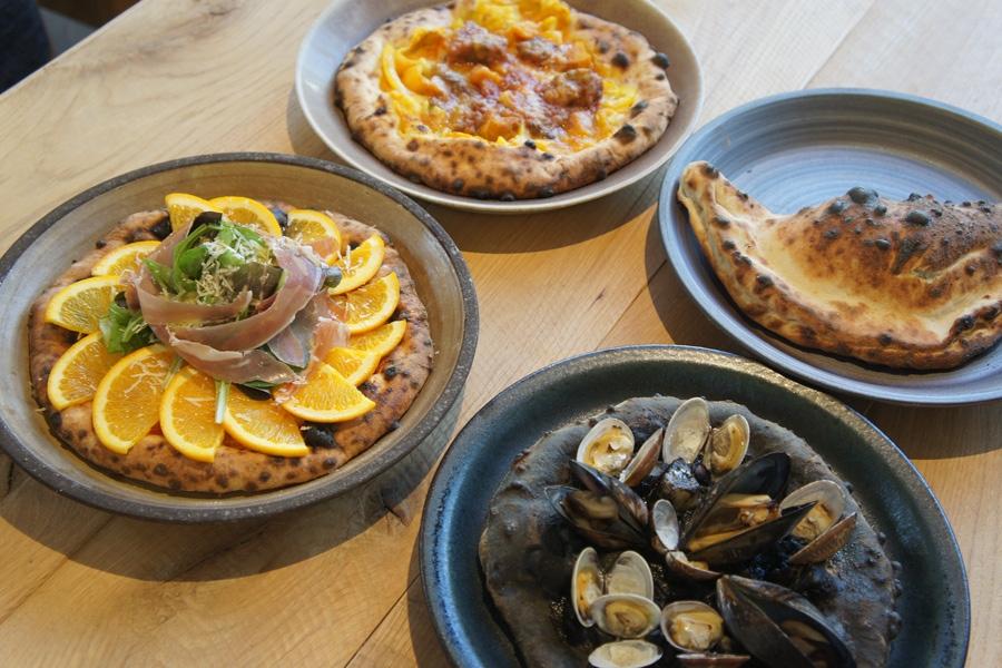 トマトソースの「太陽」、牛すじソースの「黄金」、イカスミソースの「黒」、ボロネーゼ&辛口トマトソースの「地底」という4種のピザ(各1300円・税別)