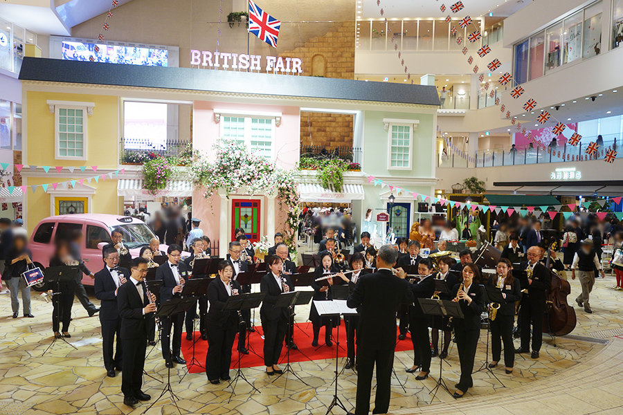 阪急百貨店吹奏楽団がオープニングでメドレーを披露。ピンクのタクシー前で記念撮影する人も続出した