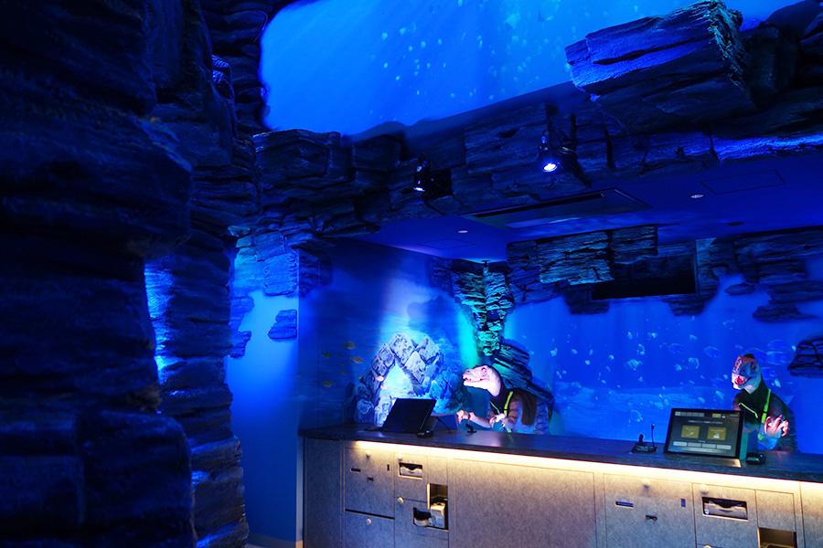 深海をイメージしたフロントで出迎えてくれる恐竜ロボット。自動チェックイン機を案内してくれる