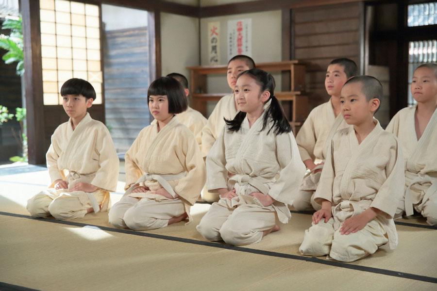 柔道の練習が始まり、草間宗一郎に礼をする子どもら