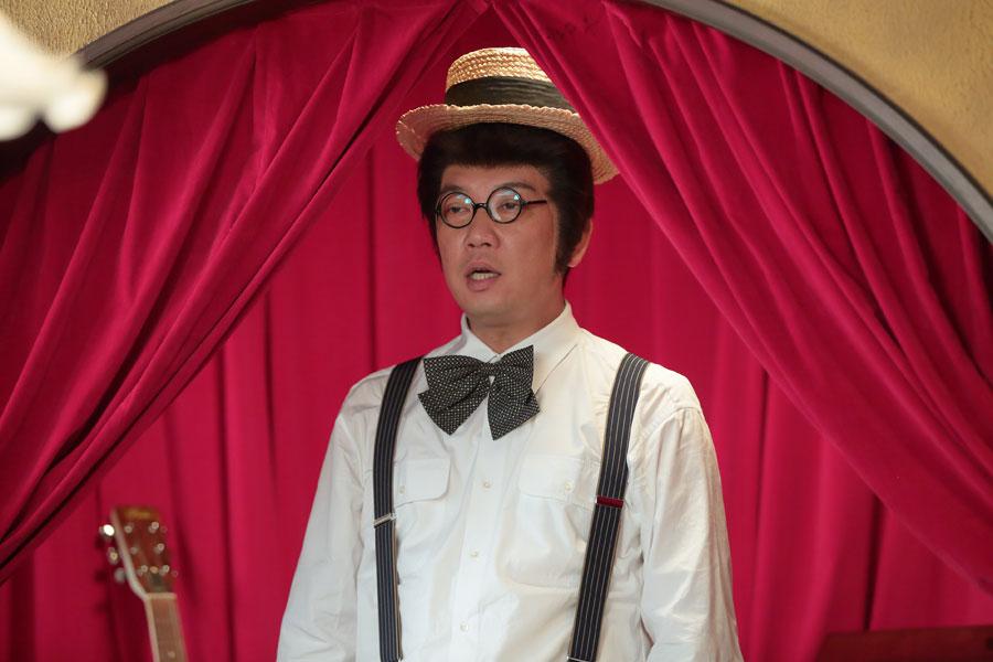 カツラをかぶり、歌える喫茶「さえずり」で歌を披露する雄太郎(木本武宏)