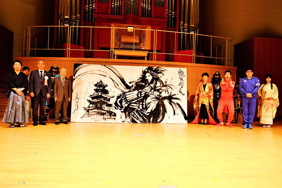 キャンペーンのロゴを制作した墨絵師・御歌頭(おかず)が描いた作品とともに記念撮影
