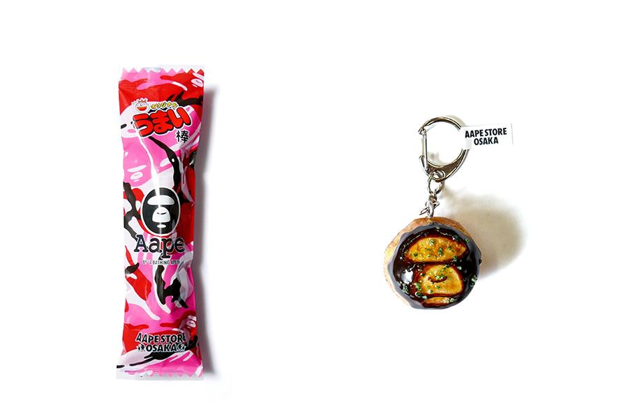 左からオリジナルデザインの「うまい棒」、たこ焼きモチーフのAAPEムーンフェイスのキーホルダー(共にノベルティ)