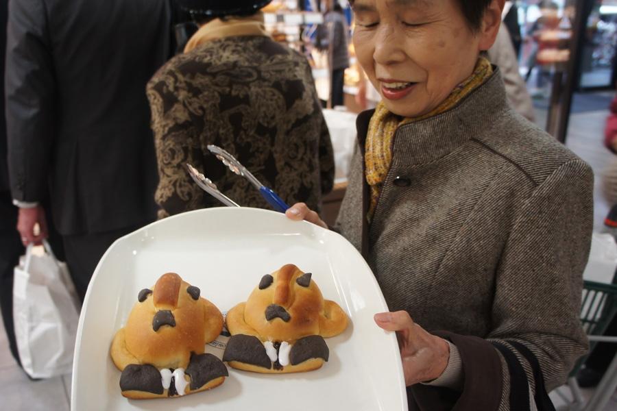 スーツやネクタイなど、細かいところまで再現されている「ハニワ部長パン」を購入する女性(27日・高島屋堺店)