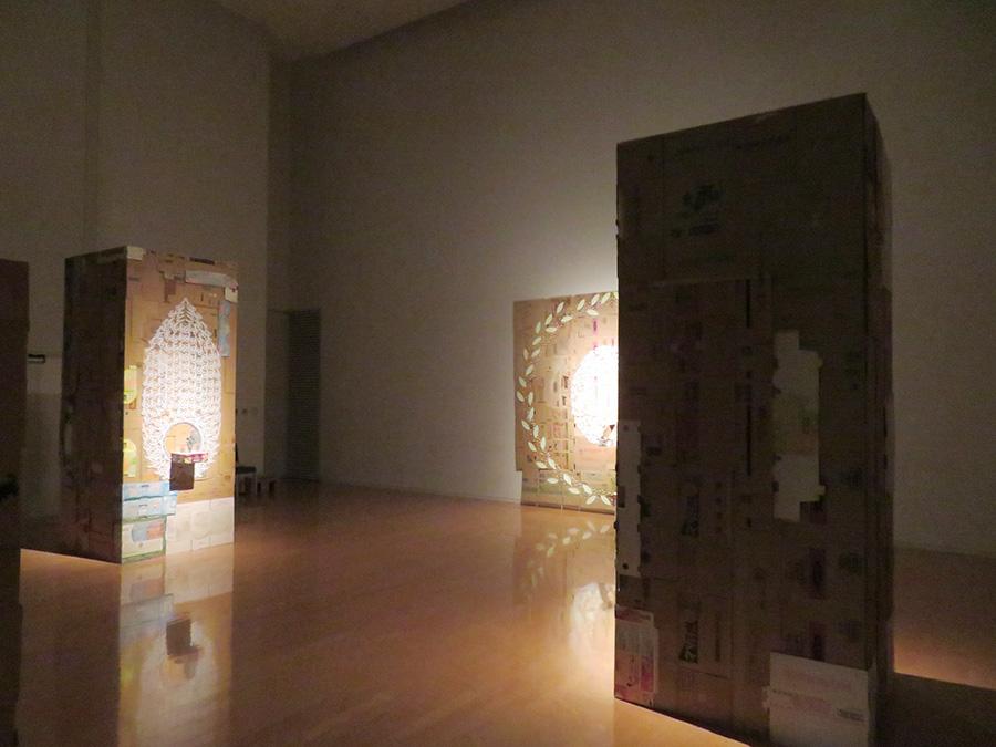 「入江早耶展」会場風景。ダンボールを組み合わせた箱とパネルの中央に、物語の主人公である3人のフィギュアが設置されている