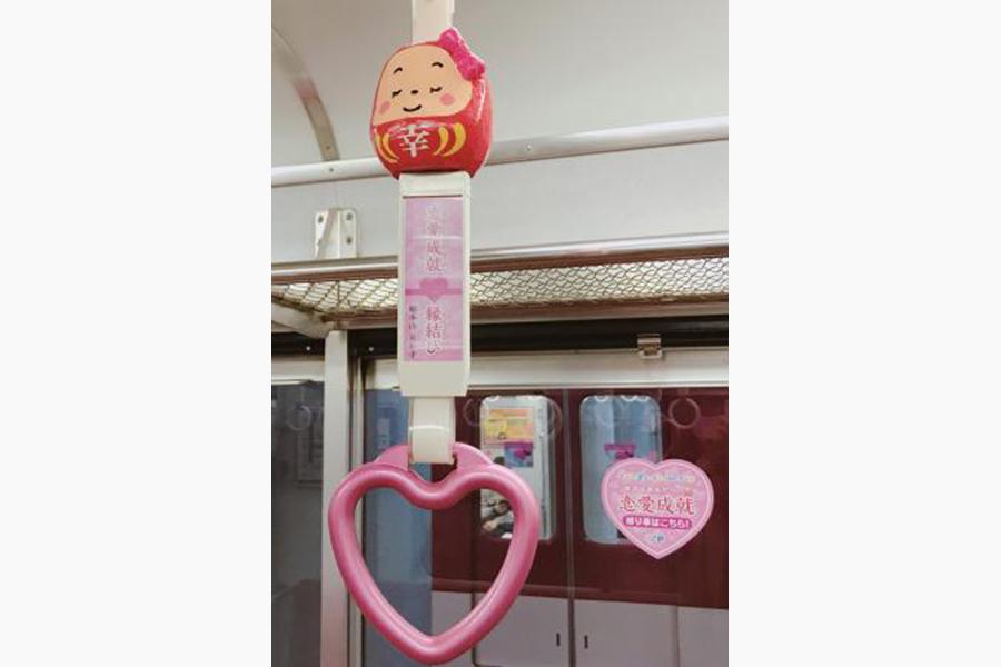 縁起の良いだるまの装飾が施され、運気の種類ごとに吊り革のモチーフも異なる。「恋愛成就吊り革」はハート型の持ち手