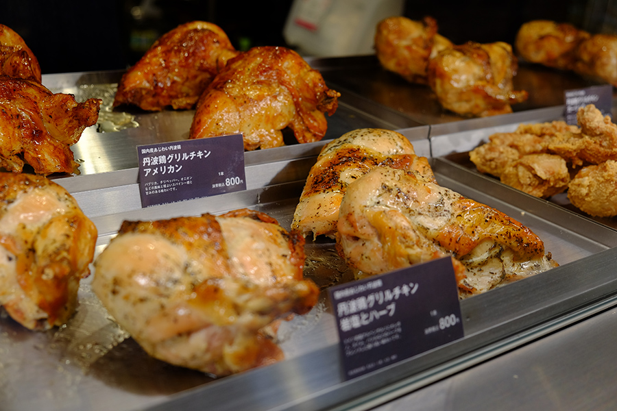 「ロイヤルチキンまるとく」で、店内の厨房で焼き上げる熱々のグリルチキンは、ハーブ味と甘辛のアメリカン味の2種。焼き鳥各種(170円)なども販売