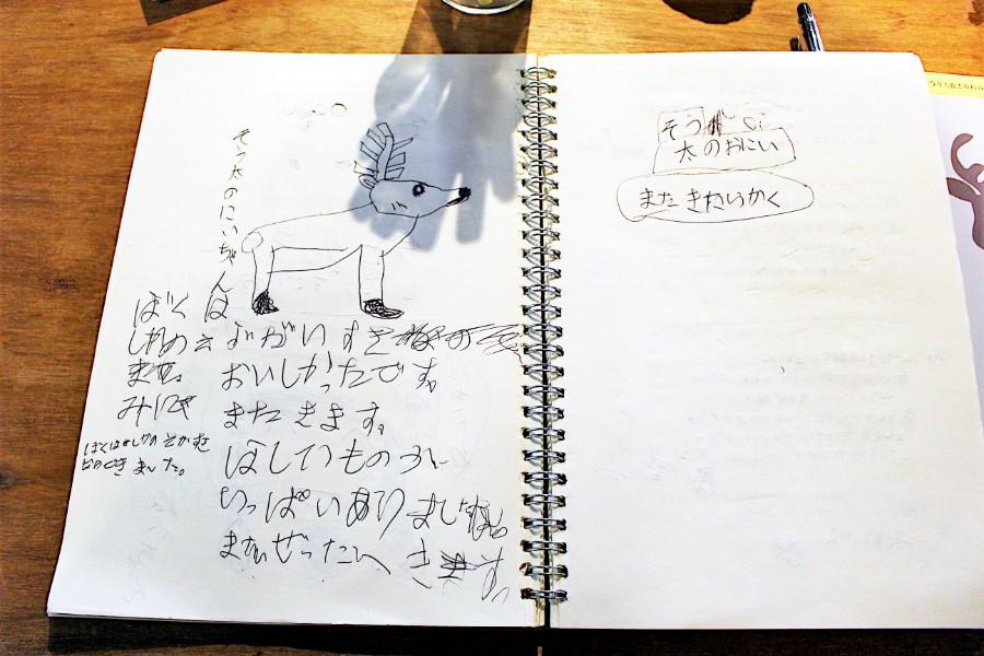 「ぼくはしかのえがすきなのできました。またきたらかく」と小さな子どもの心温まるメッセージも書かれるノート