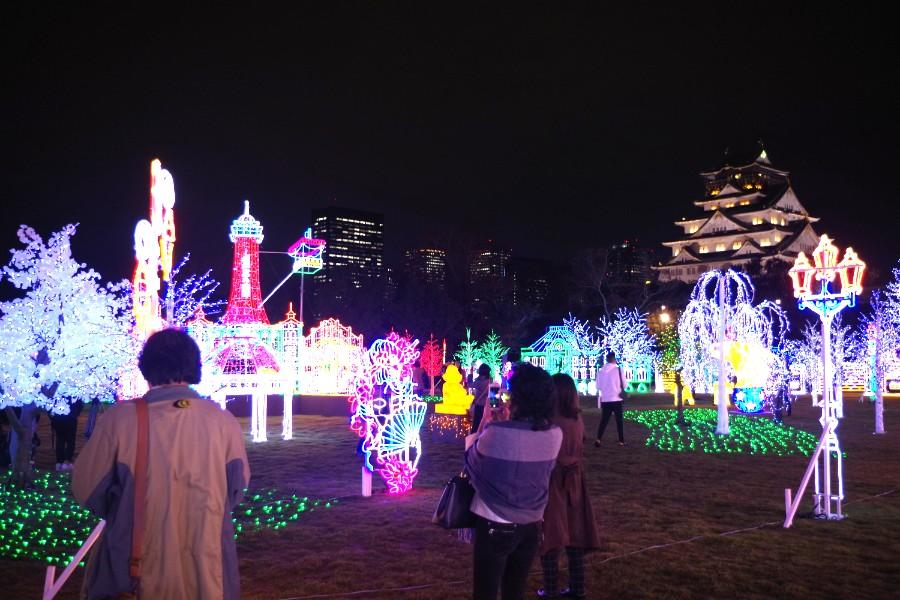 大阪城天守閣をバックにカラフルに彩られたイルミネーションを楽しむ人たち(11月22日・大阪城西の丸庭園)