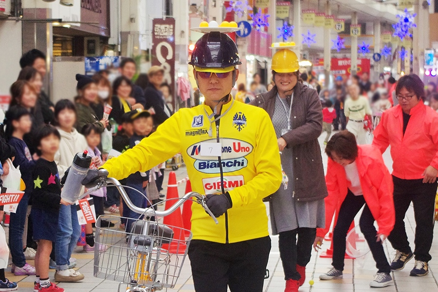 水分補給のパフォーマンスをした瞬間、頭上のピンポン玉が落下したサイクルレースウェアの参加者(24日・尼崎市内)
