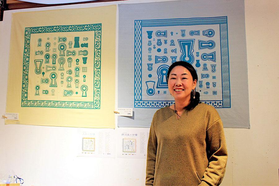 歴史意匠デザインの魅力を語るデザイナーの金田あおいさん。後ろは、奈良の古墳を配した風呂敷『大和の古墳』と摂津・河内・和泉の『摂河泉の古墳風呂敷』