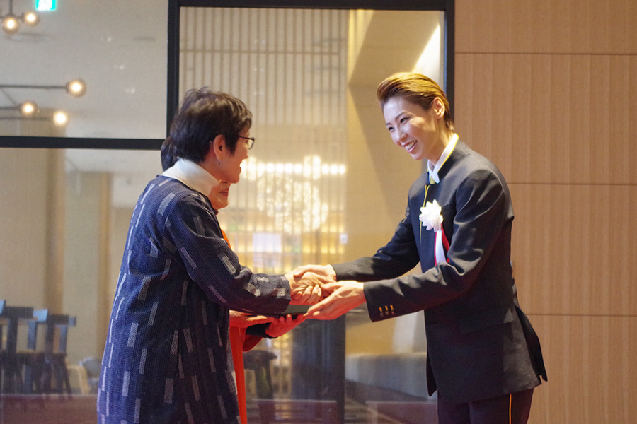 宿泊客1組目にプレゼントを贈呈し、握手する瀬戸