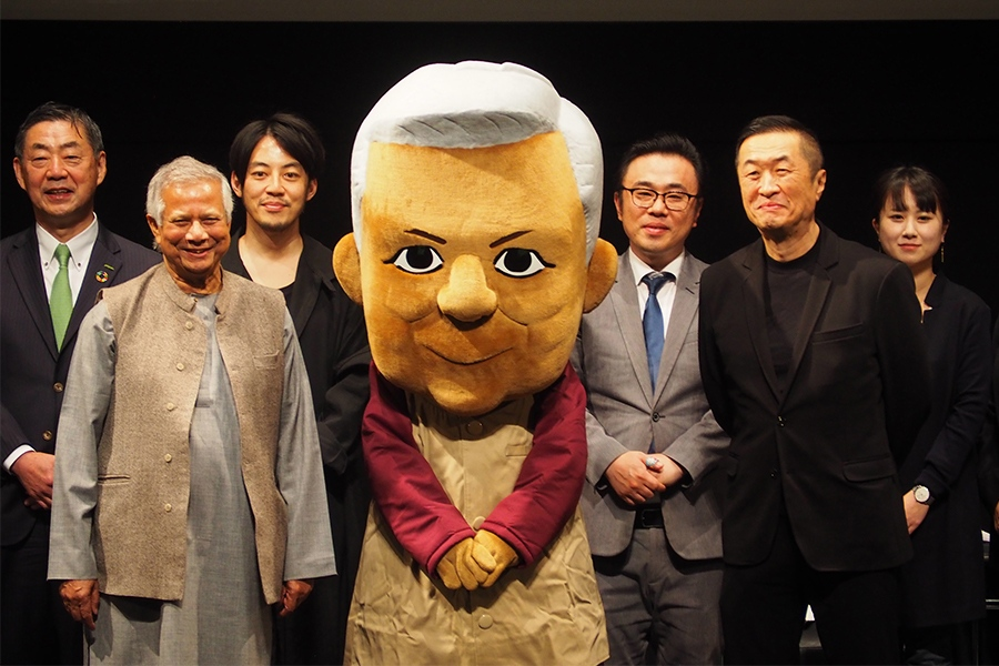 講演をおこなったムハマド・ユヌス博士(中央左)とキャラクター・ユヌスくん(22日・大阪市内)