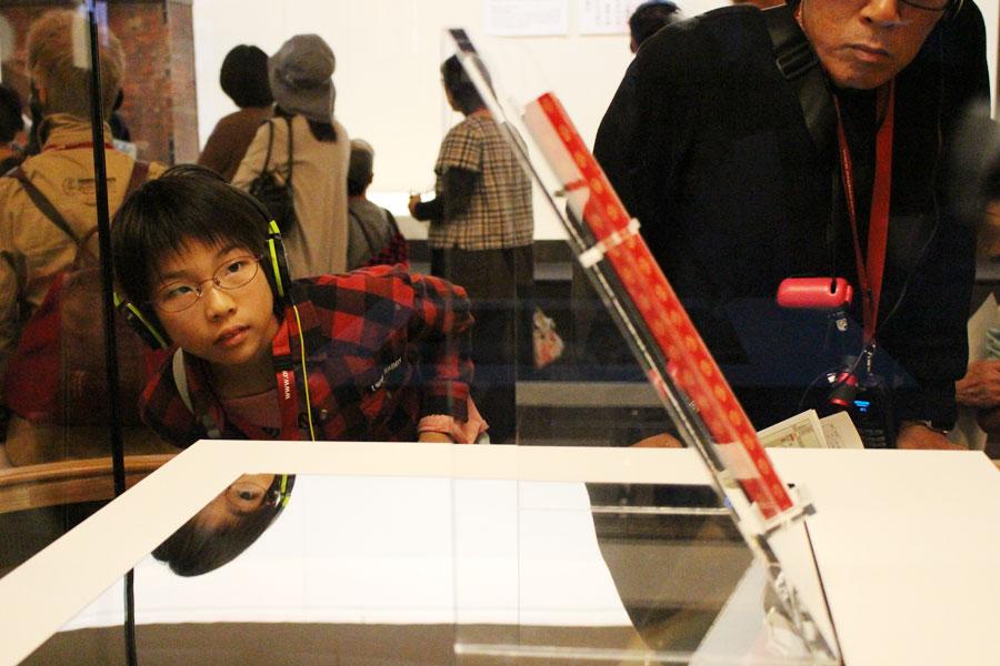 学芸員解説のあとの親子自由鑑賞で熱心に宝物を見入る小学4年生の岡田未来さん