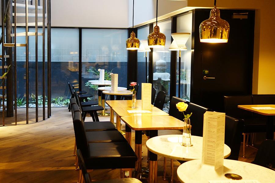アアルトがデザインした、大理石のテーブルやイスを配置した店内。窓からは、京都らしく中庭の燈籠が見える