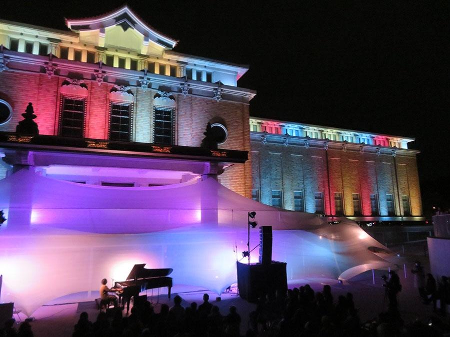 高橋匡太による本館ライトアップをバックに演奏する高木正勝。観客は極上の光と音の競演に酔いしれた