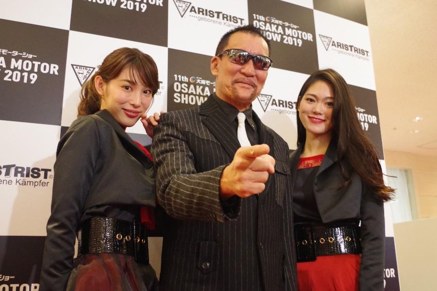ナビメイトに挟まれご機嫌な様子のプロレスラー・蝶野正洋(12月6日・インテックス大阪)