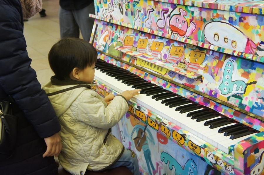 お母さんと買い物に来た2歳の男の子。初めて本物のピアノに触れてご満悦(13日・大阪市内)