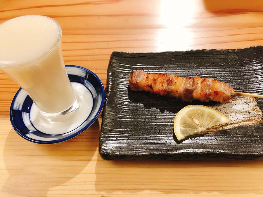 猪のバラ肉串焼き1本180円と、篠峯のどぶろく