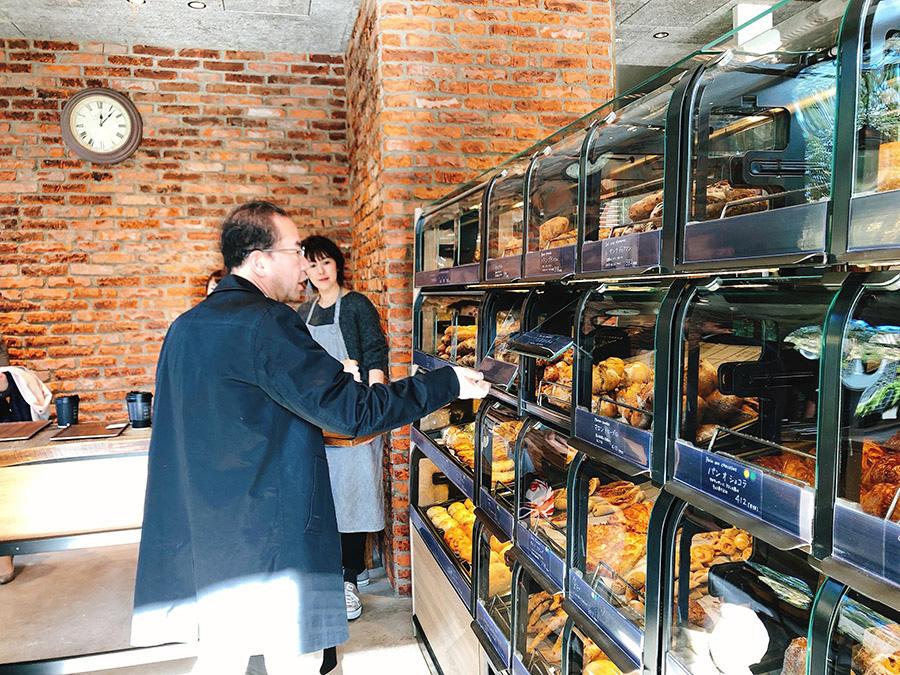 お客自身が扉を上に開け、手袋をはめた手でパンを選ぶ