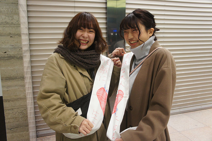 2つ繋げるとハート型になる個性的なタスキを書く仲良し女子2人。朝から元気いっぱい(13日・大阪市内)