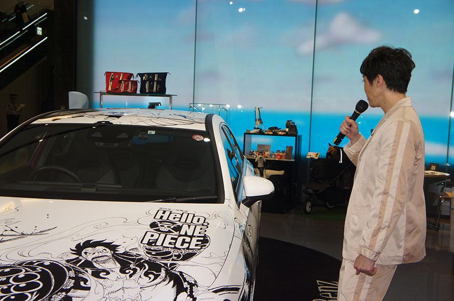 バトルシーンが描かれたラッピングカーに見入る小林よしひさ(21日・大阪市内)