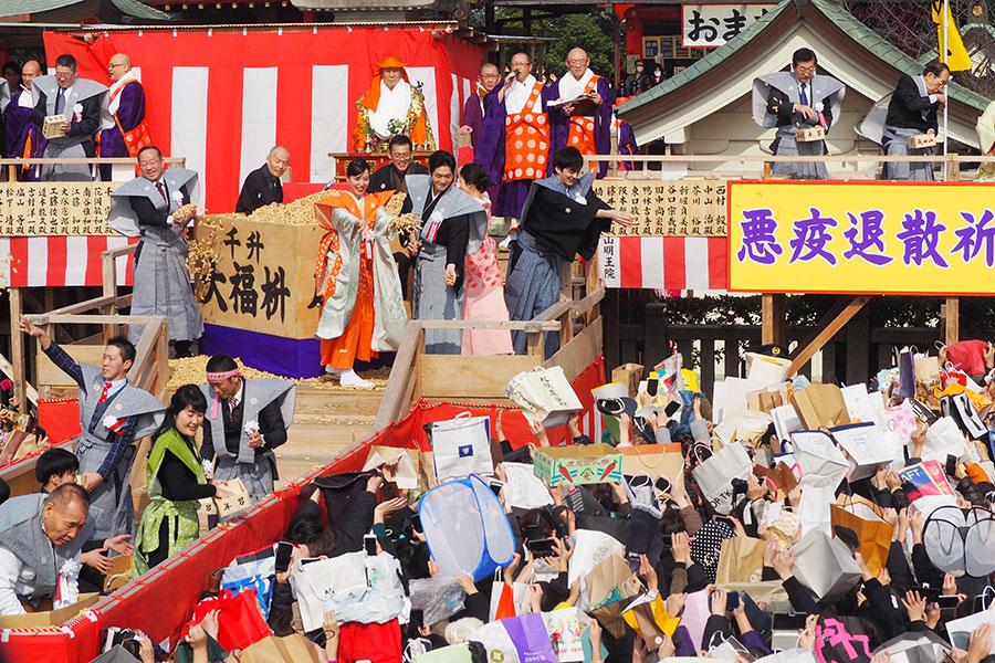 開始1時間前の時点で2万3千人以上が集まった成田山不動尊。「薪送ります」「穴窯」などドラマにまつわる切り抜きの紙袋でアピールする人も(3日・成田山不動尊)