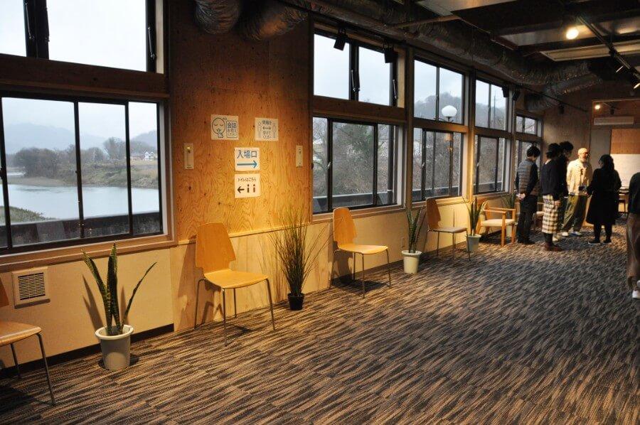 青年団の公演のセットとして使った椅子や絵を再利用したという劇場ロビーからは円山川が見える(3月28日・兵庫県豊岡市)