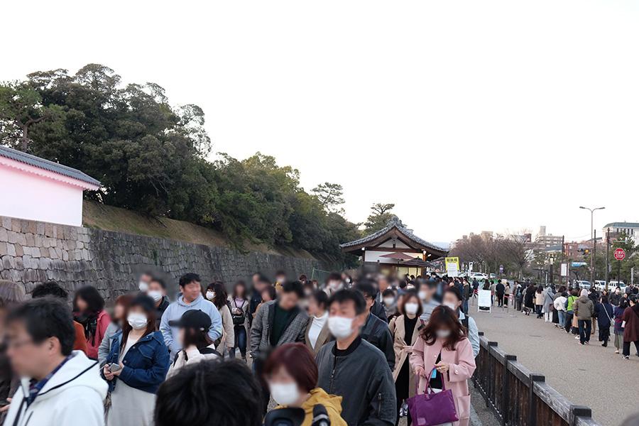 初日は、マスクを着用した人々が行列に並んだ