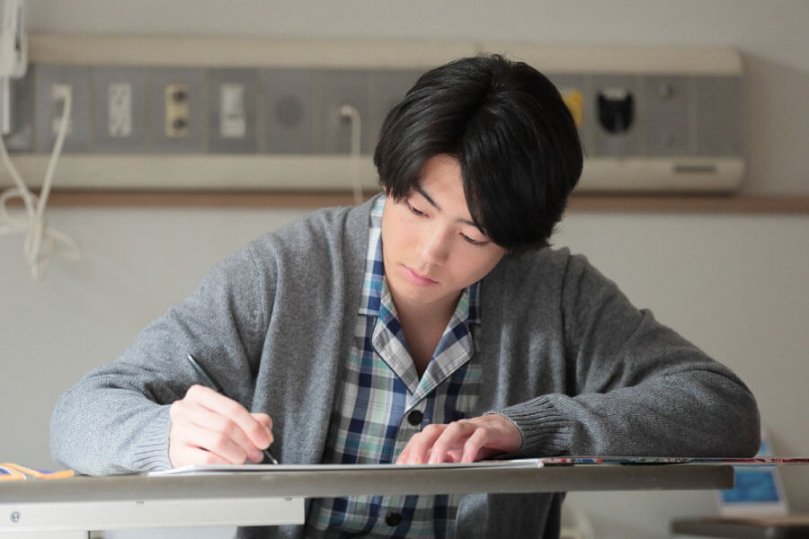 父・八郎からもらったジョージ富士川の本に何かを書く武志(伊藤健太郎)