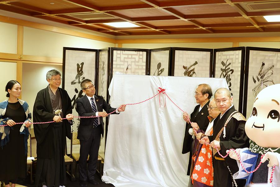 京都市長も参加した、復元羽織の除幕式の様子。左端は復元に携わった「染司よしおか」吉岡更紗さん、京友禅の老舗「千總」の仲田保司さん。右端は、大丸京都店のゆるキャラ、デッチーくん