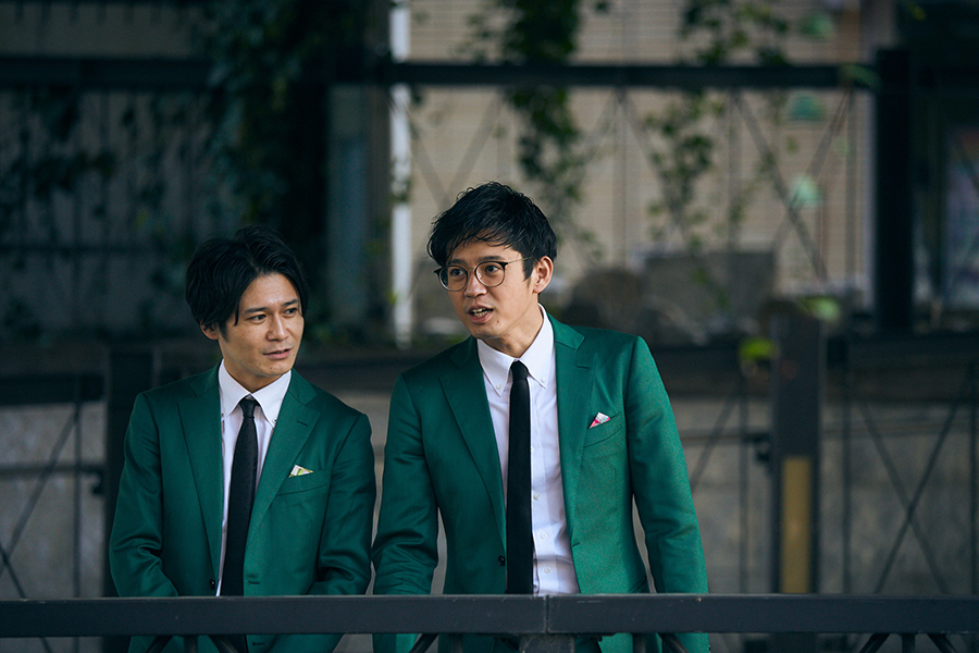 緑のスーツに身を包む2人。かつて「なんばリバープレイス」周辺で練習した当時の様子を再現してくれた
