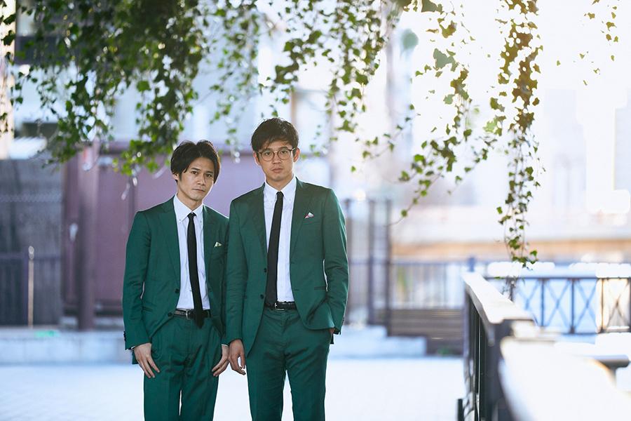 写真左から、多田智佑、桑原雅人。トレードマークは、おそろいの緑のスーツ