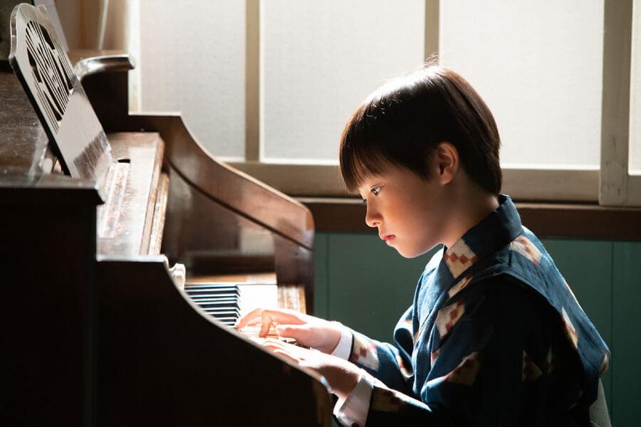 ピアノを弾く裕一(石田星空)(C)NHK