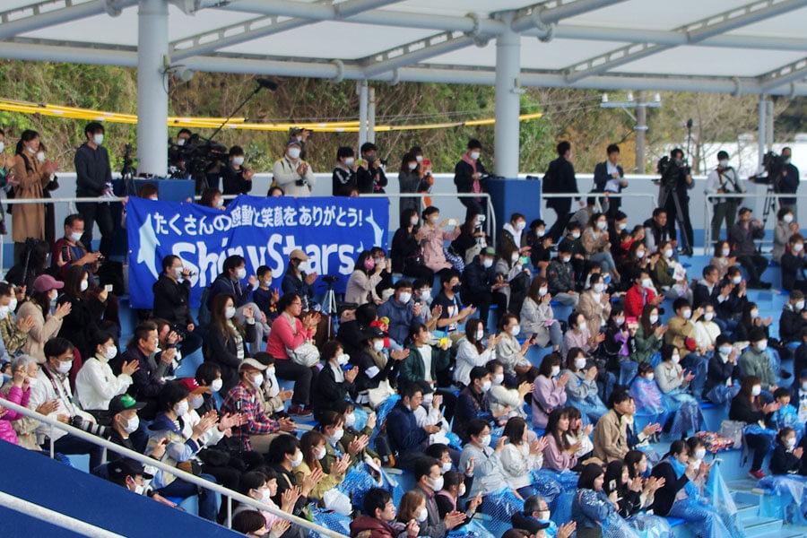 マスクを着用し間隔をとって座るイルカショー観覧席。最後には垂れ幕を掲げてシャイニングスターチームを称える人たちも(3月31日・みさき公園)