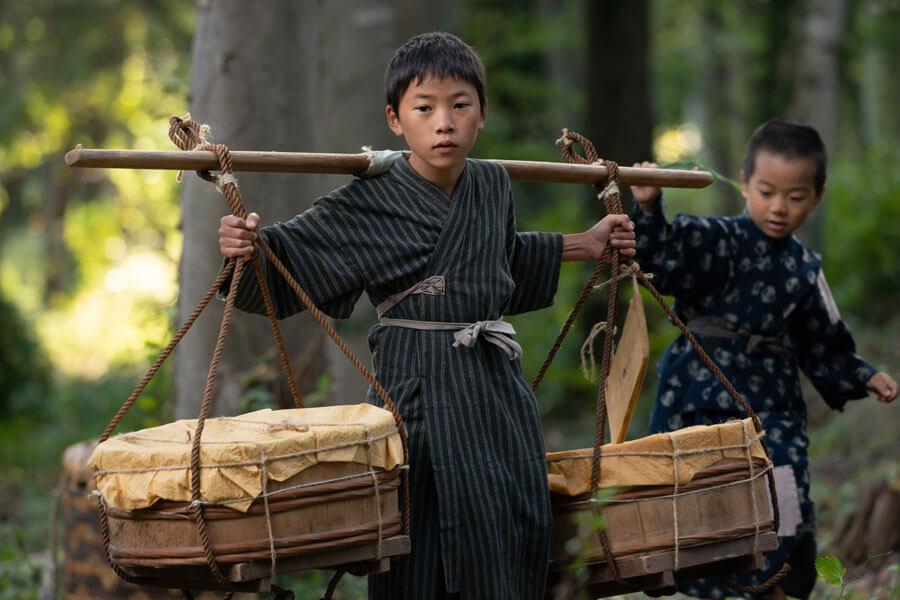 天秤棒で荷を運ぶガキ大将の村野鉄男(込江大牙) (C)NHK