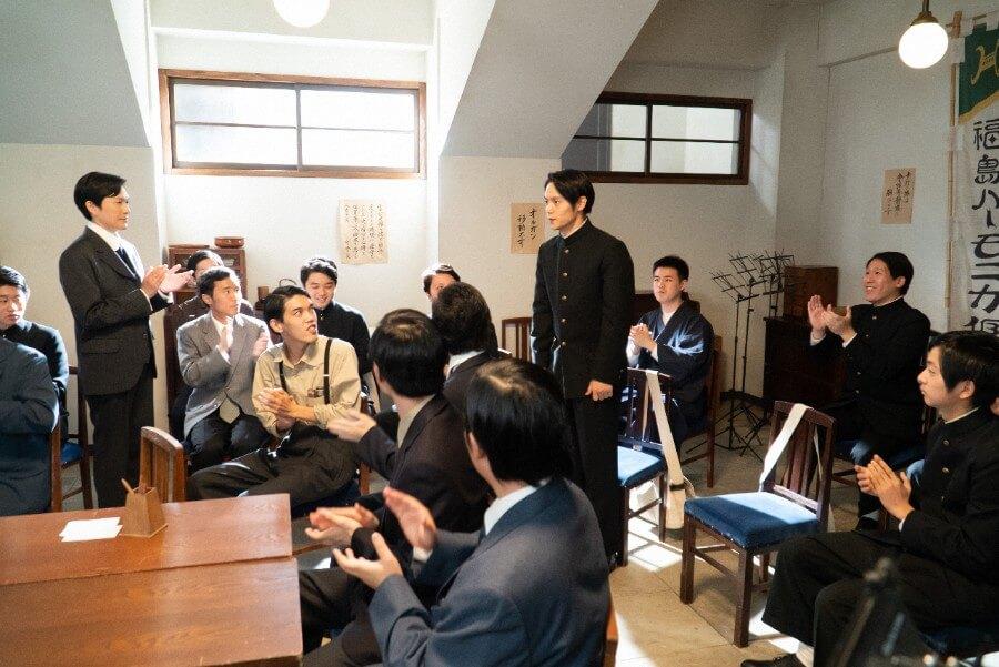 第12回より、公演曲を選ぶための投票をおこなう倶楽部のメンバーと裕一(窪田正孝)(C)NHK