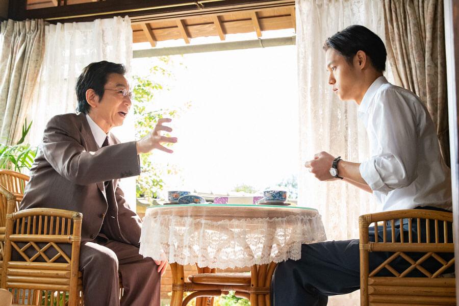 裕一(窪田正孝)にある話を持ってきた鶴亀寅吉(左/古舘伊知郎)(C)NHK