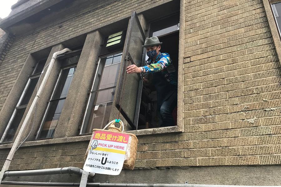2階の店からカゴを下ろすオーナーの神木慧仁さん