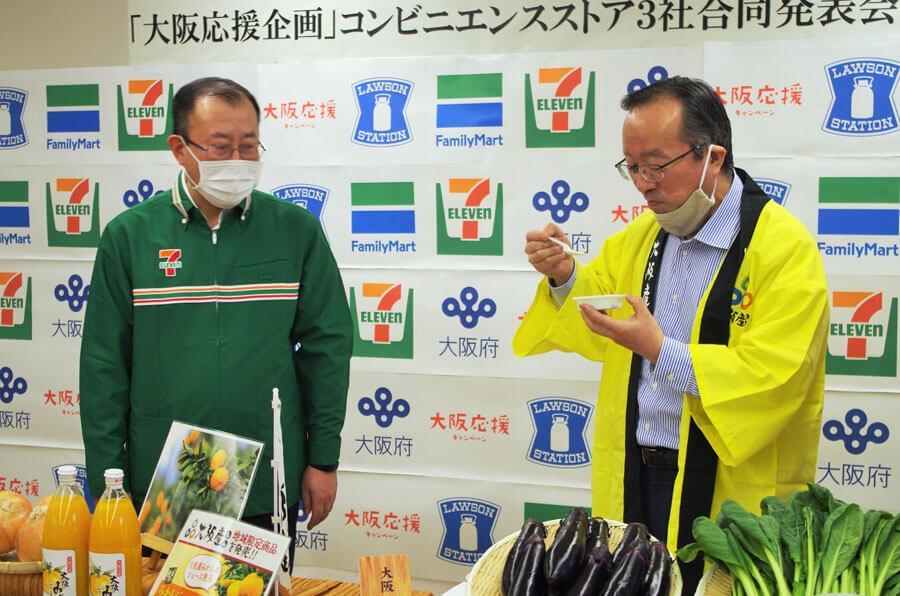 セブンイレブン・ジャパンの飯沼一丈執行役員(左)と試食する大阪府の山野謙副知事