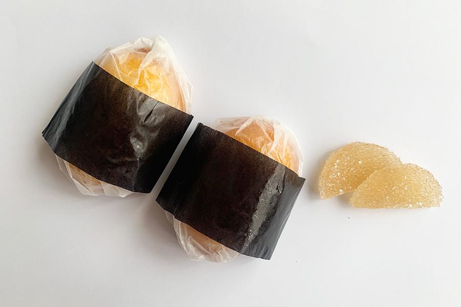 海苔に見立てた黒いペーパーを巻いたおにぎりみたいなレモンのマドレーヌ。横に添えられているのはたくわんみたいなレモンのパートドフリュイ(ゼリー菓子)