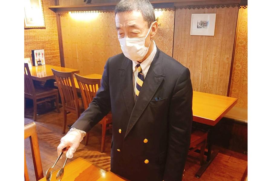 使い捨ての衛生手袋、マスクを着用して料理を取り分ける