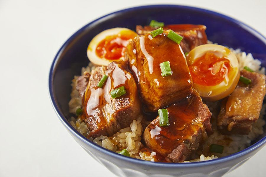 柔らかく煮込んだ三段豚バラと半熟卵黄を絡めて食べる魯肉飯(ルーローファン)