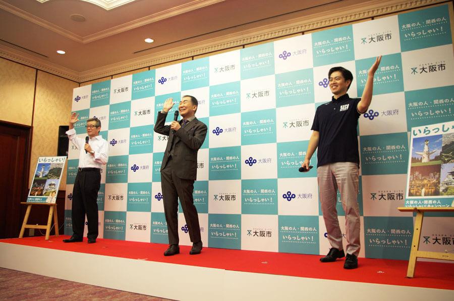 『大阪の人・関西の人 いらっしゃい!』セレモニーで「いらっしゃーい」を披露する3人と1羽。左からと松井一郎市長、桂文枝、吉村洋文知事(6月16日・大阪市)