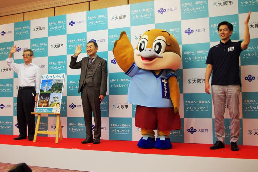 『大阪の人・関西の人 いらっしゃい!』セレモニーで「いらっしゃーい」を披露する3人と1羽。左からと松井一郎市長、桂文枝、もずやん、吉村洋文知事(6月16日・大阪市)