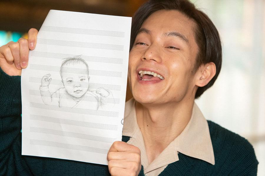 娘の似顔絵を見せながら、かわいさを自慢する裕一(窪田正孝)(C)NHK