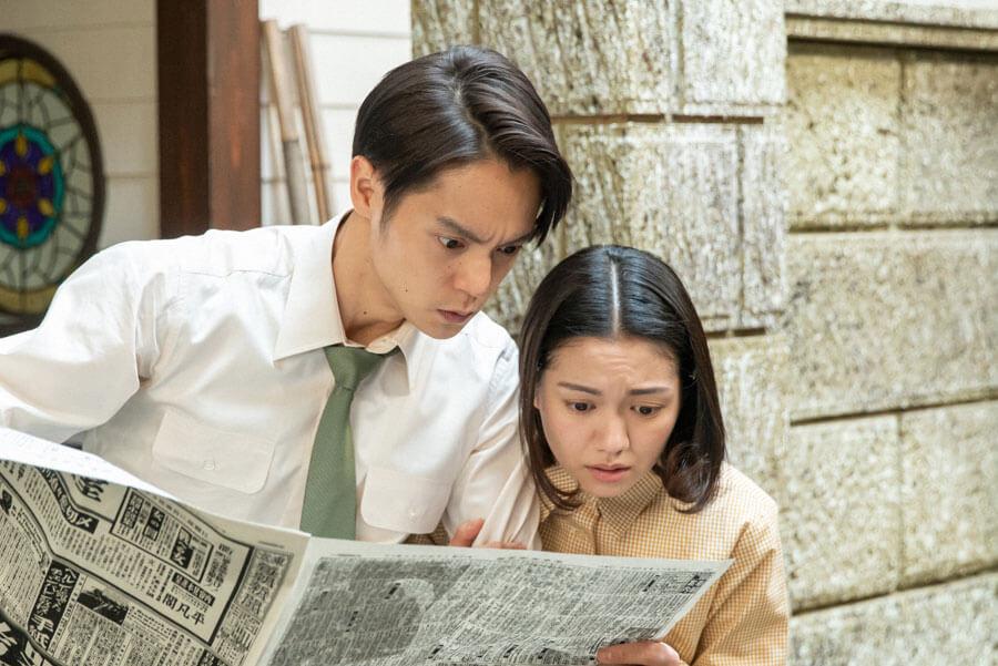 新聞を覗き込む裕一(窪田正孝)と音(二階堂ふみ)(C)NHK
