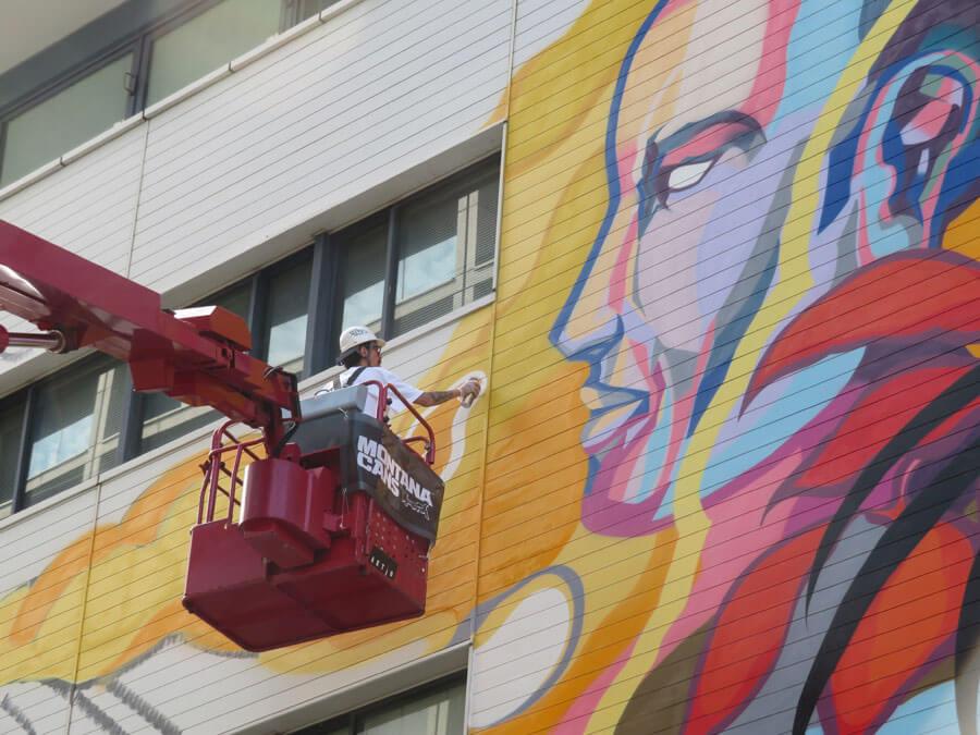 自身で作業台を動かしながら、大きな壁にスプレーでペイントするチチフリークさん(7月18日・神戸市)
