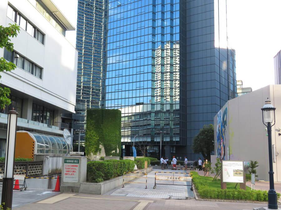 左側が2号館の北面、右側が旧花時計広場の仮囲い。完成すると両面がアートに囲まれる(7月18日・神戸市)